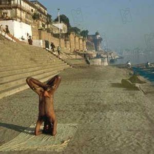Image tirée du documentaire Ayurveda de Pan Nalin où on voit un homme enduit de boue dans une posture entièrement à l'envers soutenue uniquement par la force des épaules et des bras